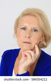 Portrait of a beautiful seventy year old lady with a serious worried expression. Studio shot, isolated on white.