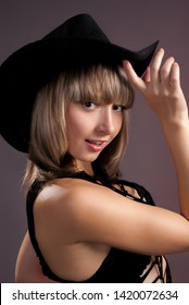 Portrait of the beautiful sexual girl of the blonde in stetson pose in studio on pink background