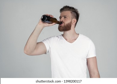 Portrait of a beautiful sexy bearded man dressed in a white T-shirt and drinking beer. he stands in front of the white background.