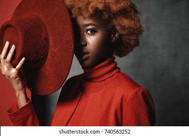 Portrait of beautiful sexy black female model wearing red sweater and jacket, holding red hat in her hand in studio with grey background