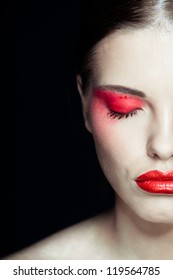 Portrait of a beautiful sexy brunette girl with red lips and red eyes