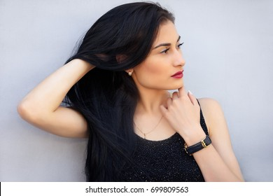 Portrait of beautiful sexy brunnete girl touching her hair and smiling, on gray background.  Pretty girl model touches her hair. A brunette woman in a black dress on wood background