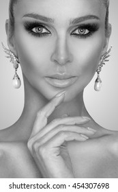 Portrait of the beautiful sexy elegant woman with amazing eyes and a perfect face in a beautiful makeup and perfect skin and nails manicured and silver earrings with pearls, jewelery