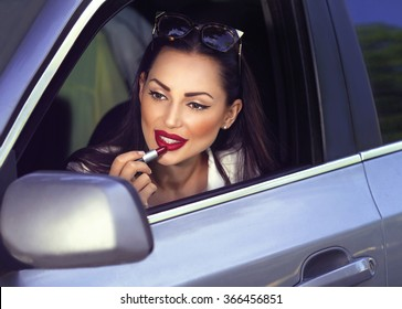 Portrait of beautiful sexy fashion girl model with red lips put lipstick looking in a mirror  driving car