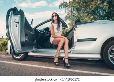 Portrait of beautiful sexy fashion woman model in white dress and luxury accessories sitting in luxury car. Young woman driving on road trip on sunny summer day. road trip.