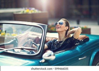 Portrait of beautiful sexy fashion woman model in sunglasses sitting in luxury retro cabriolet car