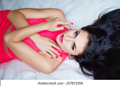 Portrait of a beautiful sexy girl brunette with blue eyes in a red dress lying on the bed, close up