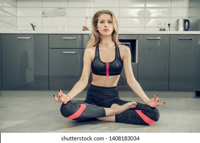 Portrait of a beautiful sexy girl is practicing yoga on the floor in the kitchen at home. Fitness at home, yoga.