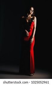 Portrait of a beautiful sexy girl in red long dress over dark background. Beauty, fashion. Studio shot.