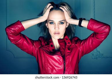 Portrait of beautiful sexy girl wearing red coat with hands over head