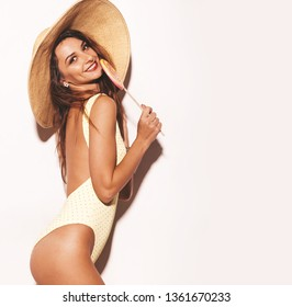 portrait of beautiful sexy smiling brunette woman. Girl dressed in casual summer yellow body lingerie and big hat. Model isolated on white background and eating lollipop
