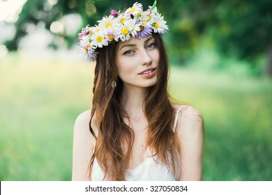 portrait of a beautiful sexy smiling girl with a wreath on his head in the spring park
