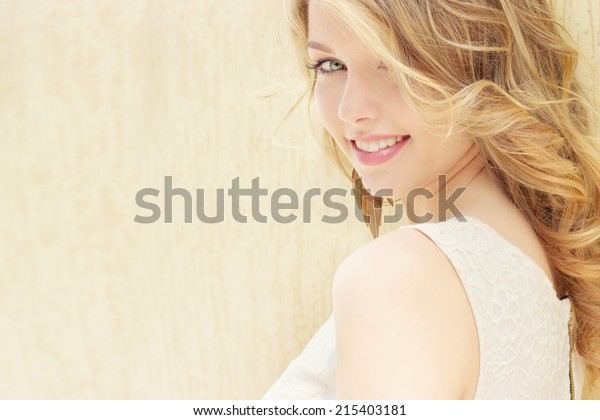 Portrait of a beautiful sexy smiling happy girl with big full lips with blond hair in a white dress on a sunny bright day
