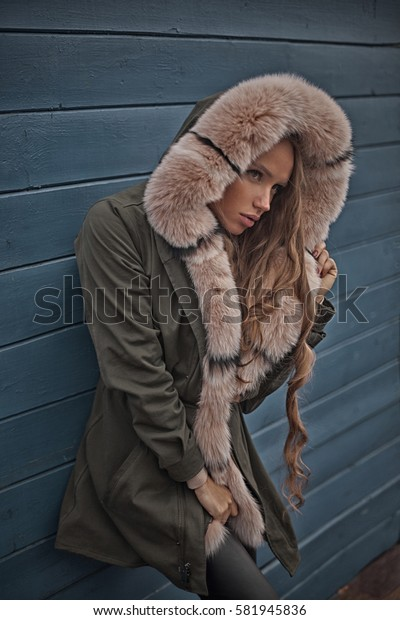 Portrait of beautiful and sexy woman in dark hood with fur