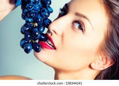 Portrait of a beautiful sexy woman with grapes.