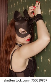 Portrait of a beautiful, sexy woman in a leather cat mask and handcuffs on a chain. BDSM