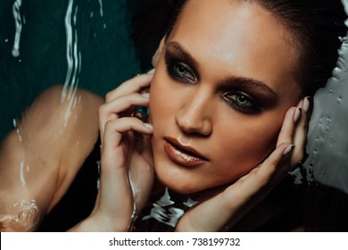 Portrait of beautiful sexy woman lies on water pool. Fingers touch the face sexually. Blue water background. Light glare and reflections on surface. Tempting looks into the frame. Silhouette of heart