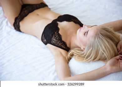 Portrait of a beautiful sexy woman in lingerie lying on the bed