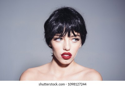 Portrait of beautiful sexy woman with perfect make-up and full lips, sensuality concept. Charming woman in black wig looking sideways isolated on gray background.
