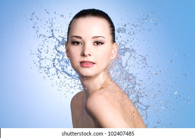 Portrait of beautiful sexy woman with splashes of water - colored background