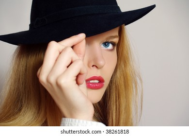 Portrait of beautiful sexy young woman with black hat