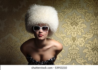 Portrait of beautiful sexy young woman in white fur hat posing over golden vintage floral wallpaper background.