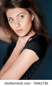 portrait of beautiful and sexy young woman in black dress with dark hair. Looking away from the camera, hand at her face, dark blue background.