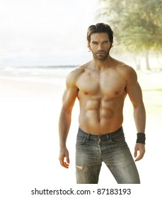 Portrait of a beautiful shirtless man in jeans relaxing outside