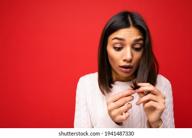 Portrait of beautiful shocked amazed young brunette woman wearing knitted jersey isolated over red background with free space and touching short hair and having split ends