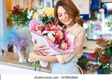 portrait of beautiful shop assistant with closed eyes hugging flowers. woman has received flowers form her boyfriend. inspiration