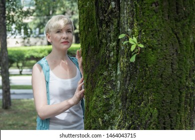 Portrait of beautiful short hair blonde woman in white clothes staying near the tree with green moss