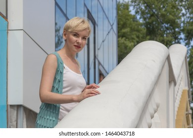 Portrait of beautiful short hair blonde woman, staying on the stairs with beautiful railings