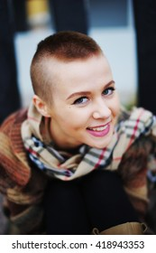 portrait of a beautiful short-haired woman in a scarf, with full lips looks wide open eyes on camera. She playfully smiling