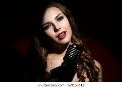 Portrait of beautiful singing woman on black background, close up