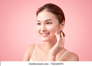 Portrait of Beautiful Skin care woman enjoy and relax touching her face on pink background