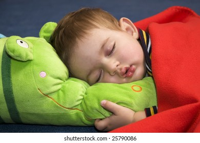 A portrait of a beautiful sleeping baby, clasping a plush toy