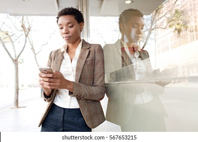 Portrait of beautiful slick african american business woman with shiny office building city reflections, thoughtful, holding smart phone outdoors. Professional black woman using technology, lifestyle.