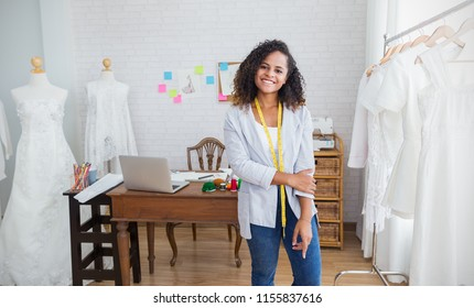 Portrait beautiful smile african american black designer woman work with computer in tailer fabric fashion small business workshop. Young owner entrepreneur creative girl textile business sme concept