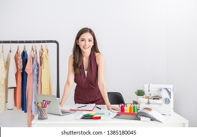 Portrait of beautiful smile asian designer woman with computer tailer fabric fashion, small business workshop. Owner startup entrepreneur. Creative girl textile garment SME business seller concept