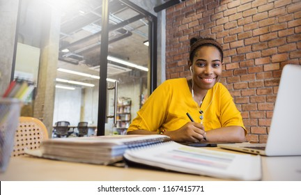 Portrait of beautiful smile black girl read books listen to earphones in library campus modern office. Young creative casual business woman working on desk with computer. Successful education concept