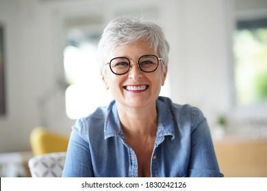 portrait d'une belle femme de 55 ans souriante aux cheveux blancs