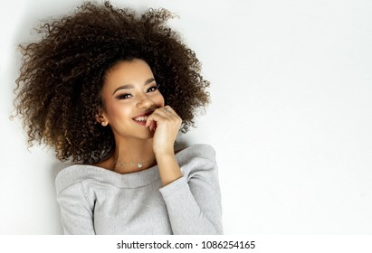 Portrait Of Beautiful Smiling Black Woman With Fresh Face, Soft Skin Having Fun Lying On White Background