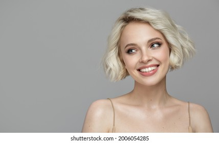 Portrait of a beautiful smiling blonde girl with a short haircut. Gray background.