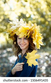 portrait of a beautiful smiling brunette girl with a wreath of yellow maple leaves on her head and in blue jersey. girl holds autumn maple leaf in hand. Golden park in the background.