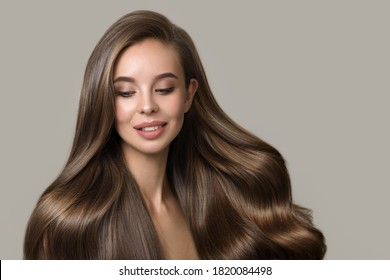 portrait of beautiful smiling brunette woman with wavy hair. Woman with hairstyle and makeup on gray background