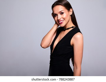 Portrait of beautiful smiling brunette woman model in black dress with evening makeup and and red lips isolated on gray