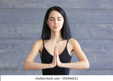 Portrait of beautiful smiling brunette young woman enjoying yoga. Yoga girl relax, breath and meditating with closed eyes on wooden background on studio, copy space