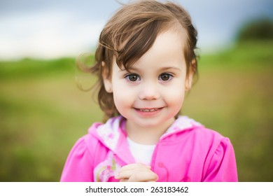 portrait of beautiful smiling carefree girl playing outdoors in field