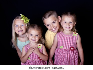 Portrait of beautiful, smiling children on a black background.