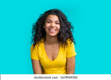 Portrait of beautiful smiling dark skinned girl wearing bright colored yellow t-shirt isolated over blue background.